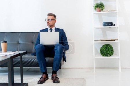 Photo pour Bel homme d'affaires en costume assis avec ordinateur portable sur le canapé - image libre de droit
