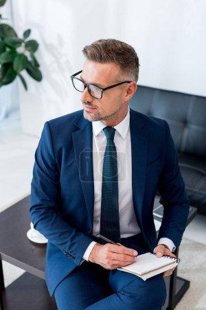 Photo pour Sérieux homme d'affaires en costume et lunettes tenant carnet et stylo - image libre de droit