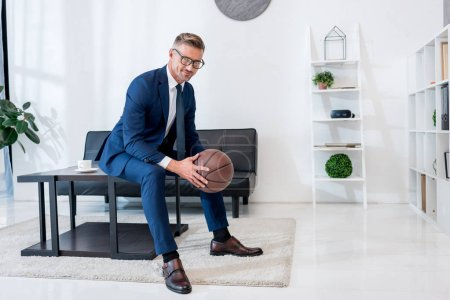 cheerful businessman in suit holding basketball in hands while sitting on coffee table
