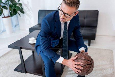 Photo pour Bel homme d'affaires en lunettes et costume tenant le basket dans les mains tout en étant assis sur la table basse - image libre de droit