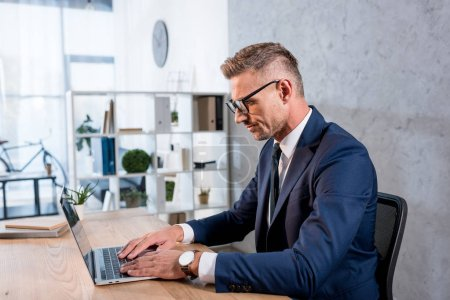 handsome businessman in glasses and suit using laptop in office