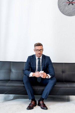 hombre de negocios en traje sentado en el sofá y sosteniendo el teléfono inteligente