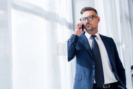 Foto de Hombre de negocios guapo en traje de pie y hablando en teléfono inteligente - Imagen libre de derechos