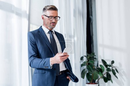 Photo for Cheerful businessman in suit and glasses standing with hand in pocket and using smartphone - Royalty Free Image