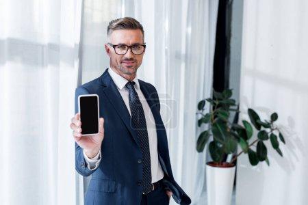 Foto de Hombre de negocios guapo en traje y gafas con smartphone con pantalla en blanco - Imagen libre de derechos