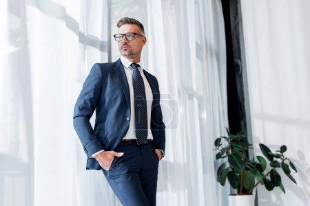 Photo pour Homme d'affaires confiant en costume et lunettes debout avec les mains dans les poches - image libre de droit