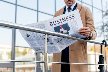 Photo for Cropped view of businessman standing in beige coat and reading business newspaper - Royalty Free Image