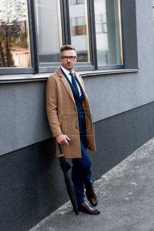 Photo pour Bel homme d'affaires en lunettes debout en manteau beige avec jambes croisées et parapluie - image libre de droit
