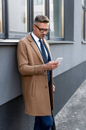 serious businessman in glasses looking at smartphone while standing in beige coat near building