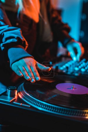 Photo for Cropped view of dj woman touching vinyl record in nightclub - Royalty Free Image
