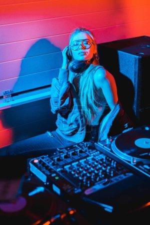 Photo pour DJ femme écoute la musique dans les écouteurs assis avec les yeux fermés - image libre de droit