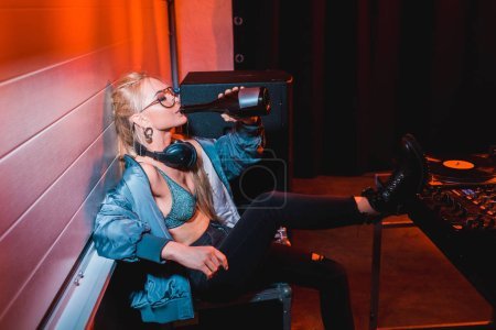 Photo for Attractive dj girl drinking from bottle while sitting in nightclub - Royalty Free Image