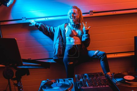 Photo for Happy blonde dj girl in glasses standing and gesturing in nightclub - Royalty Free Image