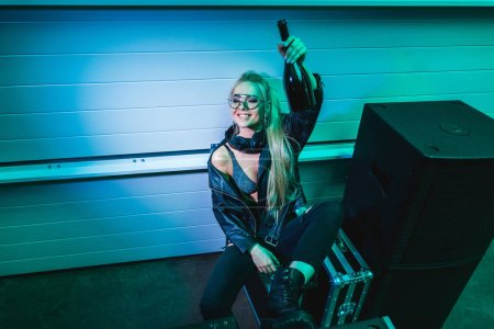 Photo for Cheerful dj girl holding bottle with wine in hand and smiling in nightclub - Royalty Free Image