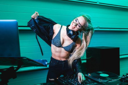 Photo for Cheerful blonde dj girl in glasses taking off jacket in nightclub - Royalty Free Image