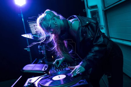 attractive blonde dj girl touching vinyl record in nightclub