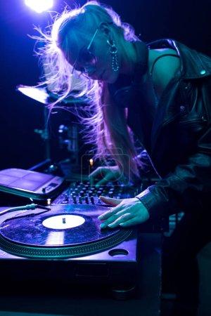 beautiful blonde dj girl touching vinyl record in nightclub