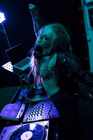 Photo pour Belle blonde dj fille dansant près dj mixer en boîte de nuit - image libre de droit