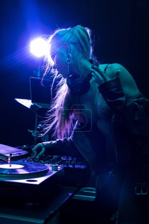 Photo pour Blonde élégant dj fille toucher dj mixer dans la boîte de nuit - image libre de droit