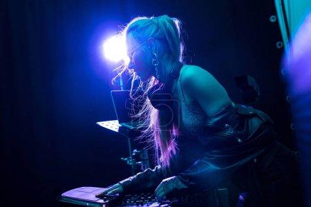 Photo pour Fille blonde dj élégant toucher l'équipement de dj en discothèque - image libre de droit