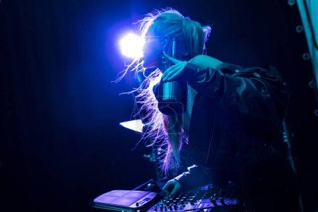Photo pour Blonde élégant dj fille toucher équipement dj tout en tenant bouteille dans la boîte de nuit - image libre de droit
