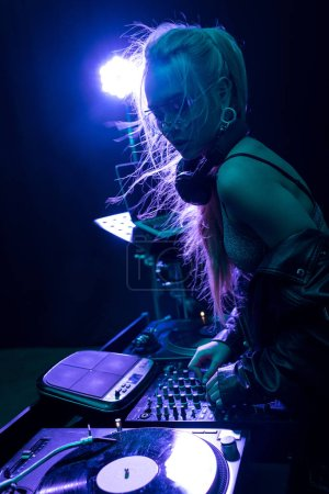 Photo for Stylish dj girl touching dj equipment while standing in nightclub - Royalty Free Image