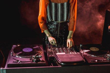 cropped view of dj girl touching dj equipment in nightclub with smoke