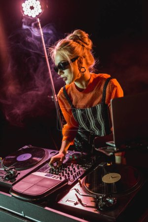 dj girl in sunglasses touching dj equipment in nightclub with smoke