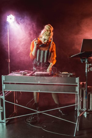 cheerful and stylish dj girl in headphones looking at dj mixer in nightclub with smoke