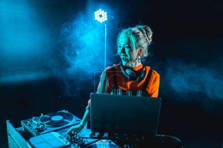 Photo pour Heureux dj fille dans casque debout près dj mélangeur et ordinateur portable dans la boîte de nuit avec de la fumée - image libre de droit