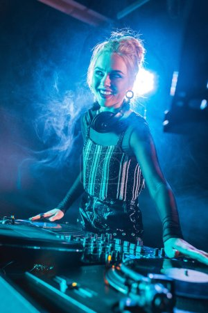 happy dj girl standing near dj mixer and touching vinyl records in nightclub with smoke