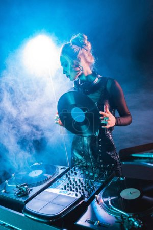 Photo for Blonde dj woman looking at dj equipment and holding retro vinyl record in nightclub with smoke - Royalty Free Image