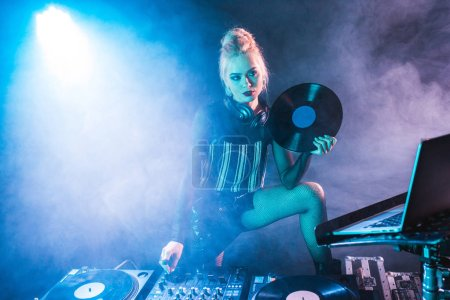 Photo for Attractive dj woman holding retro vinyl record near dj equipment in nightclub with smoke - Royalty Free Image