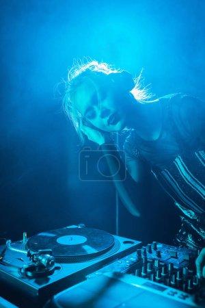 Photo for Beautiful dj girl listening music in headphones while standing with closed eyes in nightclub with smoke - Royalty Free Image