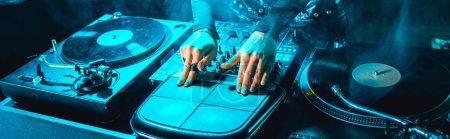 Photo pour Plan panoramique de fille dj en utilisant l'équipement dj dans la boîte de nuit avec de la fumée - image libre de droit