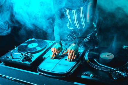 Photo for Cropped view of dj woman using dj equipment in nightclub with smoke - Royalty Free Image