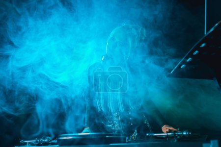 Photo for Dj girl using dj equipment in nightclub with smoke - Royalty Free Image