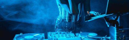 Photo pour Prise de vue panoramique de dj femme en utilisant un ordinateur portable dans une boîte de nuit avec de la fumée - image libre de droit