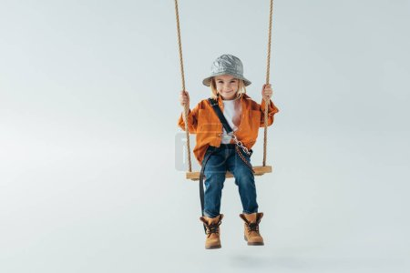 Photo for Cute kid in silver hat, jeans and orange shirt sitting on swing on grey background - Royalty Free Image
