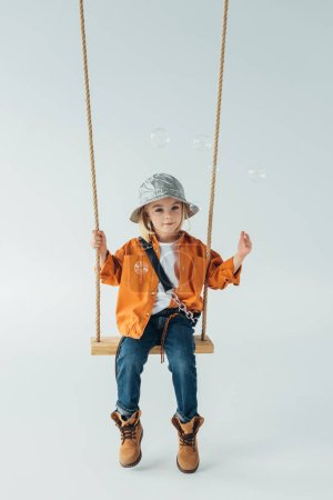 Photo for Cute kid in jeans and orange shirt sitting on swing and looking at soap bubbles - Royalty Free Image