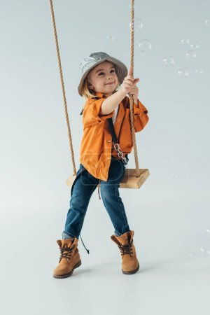Photo for Smiling kid in jeans and orange shirt sitting on swing and ponting with finger at soap bubbles - Royalty Free Image