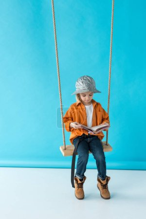 Photo for Adorable kid in jeans and orange shirt sitting on swing and reading book on blue background - Royalty Free Image