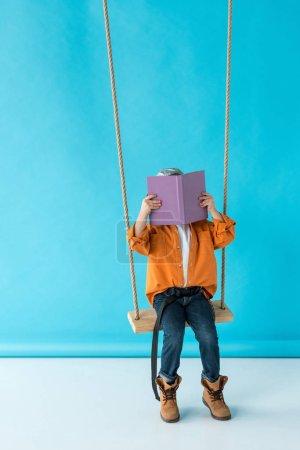 Photo pour Mignon enfant en jeans et chemise orange assis sur swing et livre de lecture sur fond bleu - image libre de droit