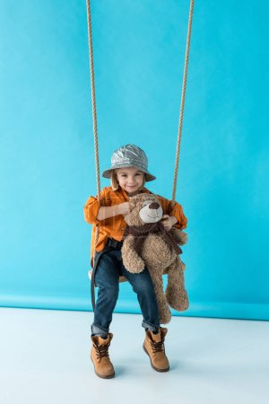 Photo for Cute kid sitting on swing and holding teddy bear on blue background - Royalty Free Image