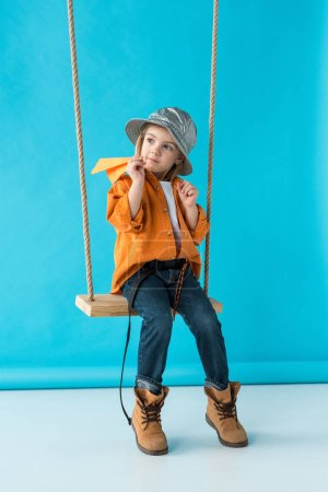 Photo for Cute kid sitting on swing, holding paper plane and looking away on blue background - Royalty Free Image