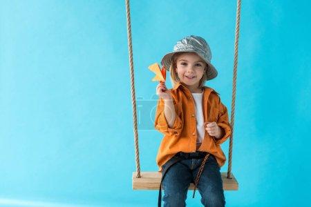 Photo pour Cute kid assis sur la balançoire, en tenant l'avion en papier et en regardant caméra isolée sur bleu - image libre de droit