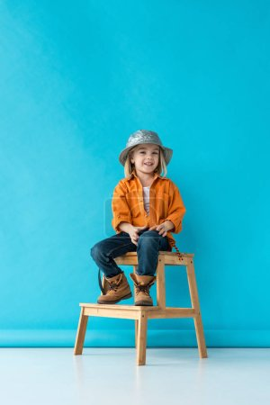 Photo for Smiling kid in jeans and orange shirt sitting on stairs and looking at camera - Royalty Free Image