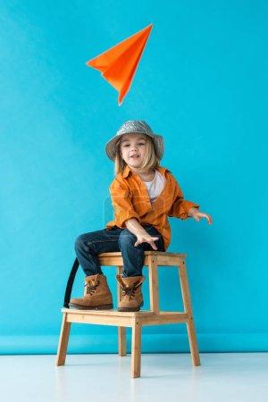 Photo pour Enfant en jeans et chemise orange assis sur les escaliers et jouer avec l'avion en papier - image libre de droit