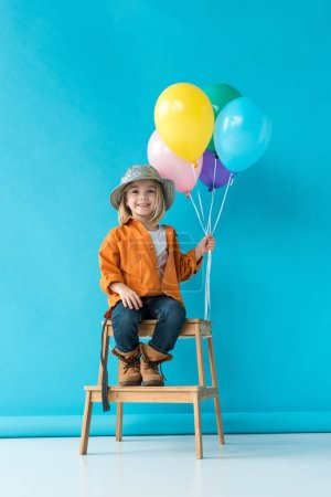 Photo for Cute kid in jeans and orange shirt sitting on stairs and holding ballons - Royalty Free Image