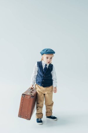 Photo for Surprised kid in retro vest and cap holding suitcase on grey background - Royalty Free Image